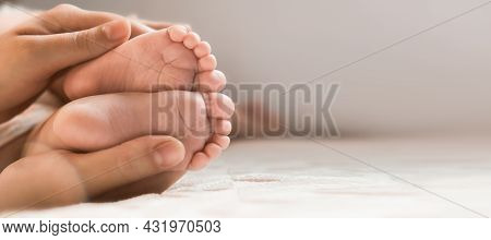 Mother Holding Baby Feet In Hands. Legs Newborn In Female Parents Hand. Small Childrens Feet In The