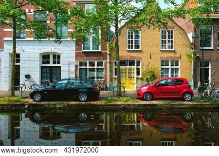 Cars and bicycles on canal embankment in street of Delft with reflection. Delft, Netherlands