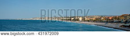 Picturesque scenic panorama of Mediterranean sea coast in Nice, France. Mediterranean Sea waves surging on the coast, people are relaxing on the beach. Nice, France
