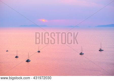 Tourist yachts boat in Aegean sea near Santorini island with tourists watching sunset from viewpoint. Santorini, Greece