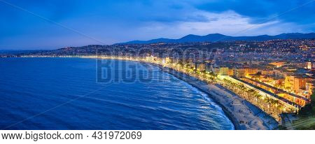 Scenic panorama of Nice, France in evening blue hour. Mediterranean Sea waves surging on coast, people relaxing on beach, lights illumination on colorful houses.
