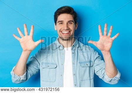 Close-up Of Handsome Man Smiling, Showing Fingers Number Ten, Standing Over Blue Background