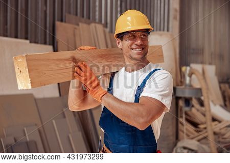Cheerful Worker Carrying Timber Wood Plank At Construction Site