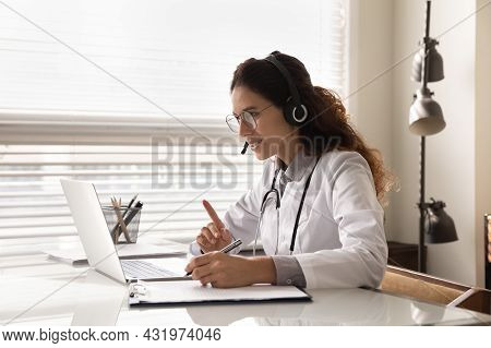 Happy Attentive General Practitioner In Headset Using Laptop
