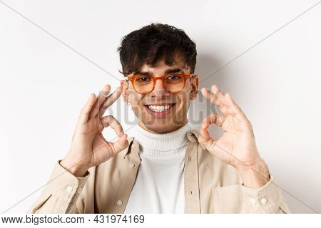 Close-up Of Handsome Guy In New Eyewear Showing Okay Signs And Smiling Pleased, Praising Good Glasse