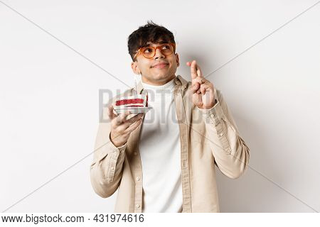 Cute Hopeful Guy In Glasses Making Birthday Wish, Holding Cake And Fingers Crossed, Looking Up And P