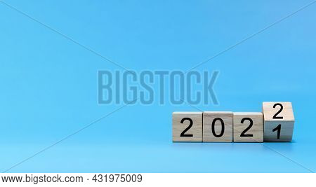 Happy New Year 2022 Celebration. Number Written On Wooden Cube Block Stack On Blue Background, Chang