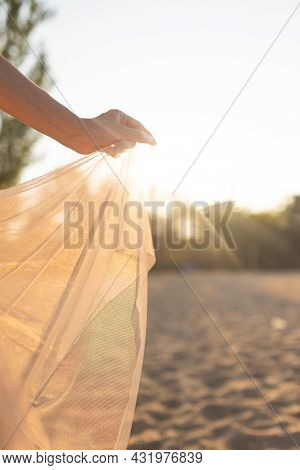 Girl Posing In A Transparent Dress At Sunset. Walks Along The Beach In The Evening