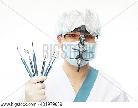 Male doctor in a surgical mask with binocular loupes and holding dental instruments, isolated on white background.