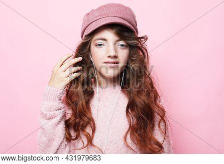Girl cute little child wear headphones listen music. Kid listen music pink background.