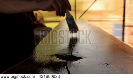 Solid Wood Texture Board With A Deep Crack And A Hollow Of A Large Knot In The Process Of Varnishing