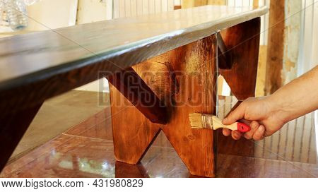 Applying Varnish On A Wooden Bench Standing On A Work Table In A Carpenter's Workshop, Varnishing A