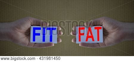Fit And Fat Creative Concept: Man Hands Holding Cards With The Words Fit And Fat.  Concept Of Health
