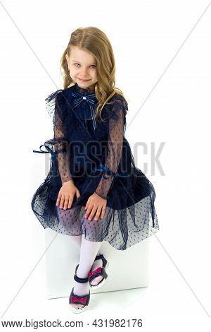Lovely Little Girl Dressed Dark Blue Nice Dress. Beautiful Child Posing For Portrait In Studio. Ador