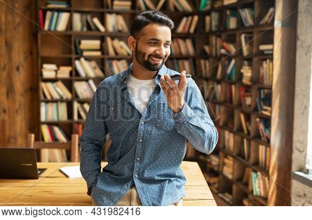 Smiling Indian Man Using Convert Voice Into Text Mobile App, Holding Smartphone, Talking Into A Mic.