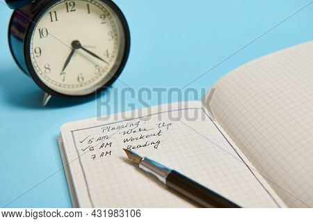 Cropped Image Of An Open Organizer With Plans For The Day, Ink Pen And Alarm Clock On Blue Backgroun