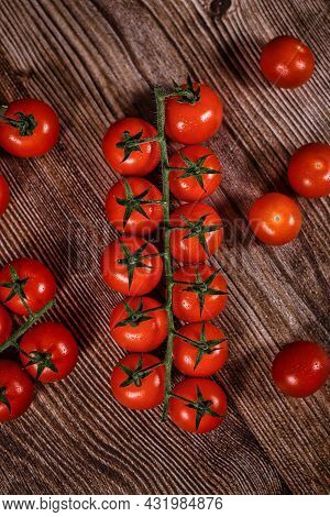 Bunch Of Trusses Of Small Ripe Cherry Tomatoes On Wooden Background