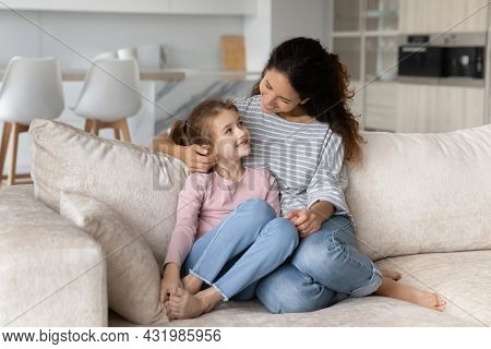 Caring Young Mother Cuddling Cute Little Kid Daughter.