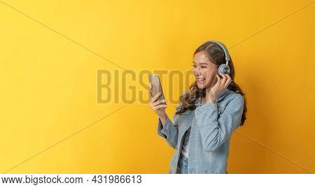 Asian Pretty Woman In Casual Clothing With Headset Listening Music With Mobile Smart Phone On Copy S