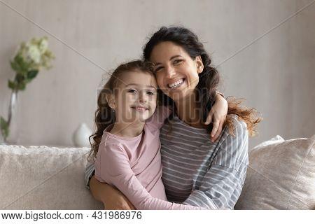 Happy Bonding Family Cuddling Sitting On Cozy Sofa.
