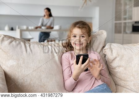 Small Girl Playing On Phone While Mommy Sitting At Kitchen.