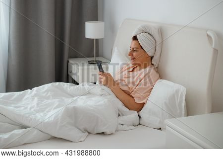 Happy Young Caucasian Woman Relax On Comfortable Bed At Home Texting Messaging On Smartphone, Smilin