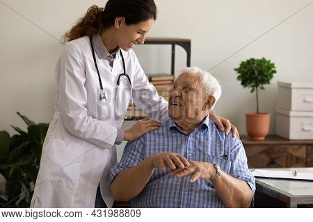 Happy Doctor Giving Hug And Support To Optimistic Old Patient