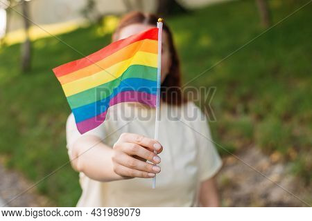 Beautiful Red Lesbian Woman With Lgbt Rainbow Flag At Sunset On Green Nature Background. Happiness,