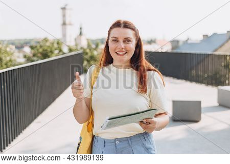 Attractive Young Female Tourist Is Exploring New City. Happy Redhead Woman With Map In Hands Showing