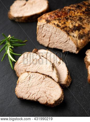 Roast Pork Tenderloin With Herbs On Rustic Stone Board