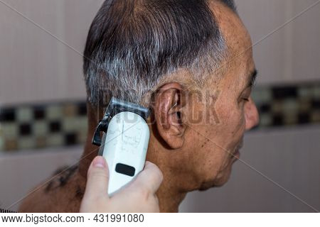 Old Man Having A Hair Cut By Hairstylist Using Electrical Battalion. Men\\\'s Hairstyling And Hair C