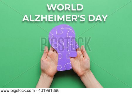 World Alzheimer's Day. Female's Hands Holding A Paper Human Head With Puzzle Ornament. Green Backgro