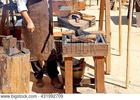 Bellows Inflate The Fire In The Coals. Master Blacksmith In Blacksmith Workshop Demonstrating Old Te