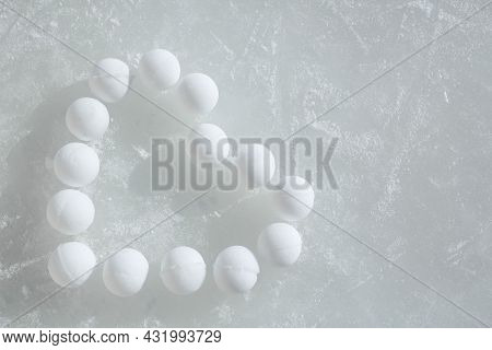 A Lot Of Snowballs Laid Out On The Ice In The Form Of A Heart. Frozen Ice In The Scratches. Copy Spa