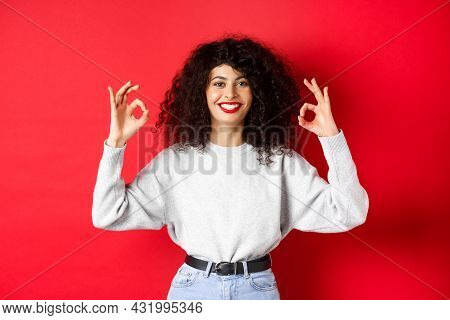 Confident Pretty Girl With Curly Hairstyle, Showing Okay Gestures And Smiling, Approve And Agree Wit
