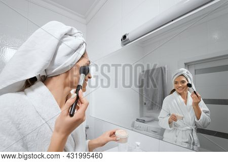 Woman Doing Makeup In Bathroom Looking At Himself In The Mirror. Concept Of Care Body.