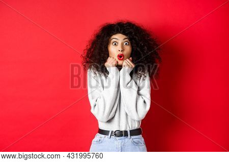 Surprised Young Woman Looking With Disbelief And Amazement At Camera, Saying Wow And Standing In Awe