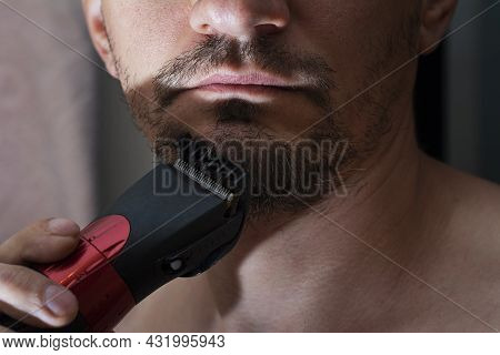 Process Cutting Beard Handsome With Trimmer. Young Caucasian Bearded Man Trimming Beard In Home Duri