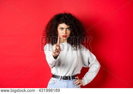 Serious Confident Woman Say No, Extend One Finger To Stop You, Prohibit Something Bad, Standing Dete