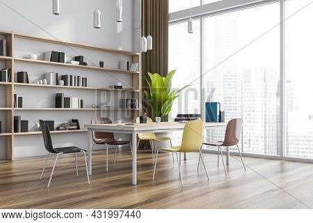 Modern Office Interior With A Collaboration Table, Bright Chairs, Pendant Lights, A White Wall, A Sh