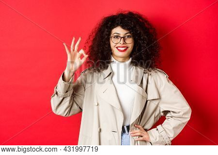 Portrait Of Confident Trendy Woman In Glasses And Trench Coat, Showing Okay Gesture To Approve Or Ag