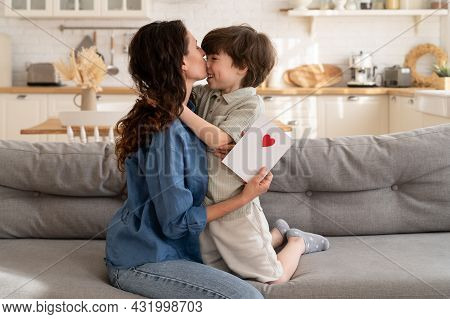 Kid And Parent Cuddling On Mother Day: Happy Mom Hugging Kiss In Forehead Small Cute Son Hold Handma