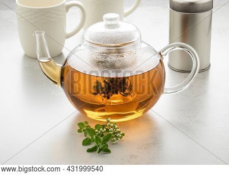 Glass teapot with oregano tea and a fresh twig of oregano in front