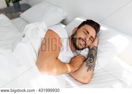 Happy Morning. Satisfied Guy Waking Up, Feeling Rested, Happy Bearded Black Guy Lying On White Linen