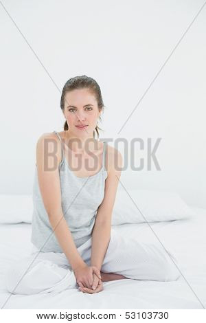 Portrait of a young woman in nightwear sitting in bed