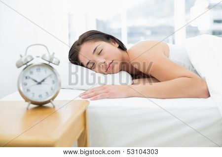 Young woman sleeping in bed with blurred alarm clock on bedside table