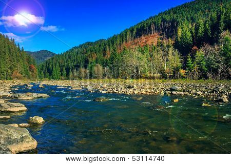 River Flows By Rocky Shore Near The Autumn Mountain Forest