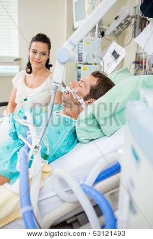 Beautiful woman looking at male patient resting on bed in hospital