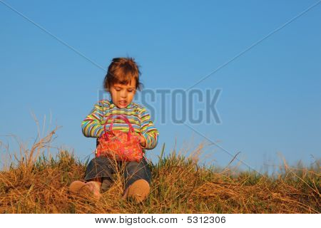 Little Girl In Striped T-shirt With Red Bag Sits On Dry Grass