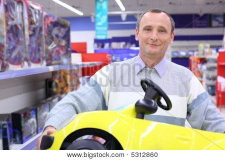 Elderly Man In Shop With Children's Car In Hands